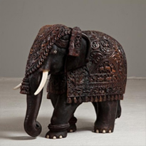 A large Indian carved hardwood elephant with bone tusks and toe nails