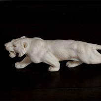 A Meiji period ivory Okimono of a stalking tiger with mother of pearl eyes