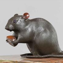A Meiji period bronze of a rat holding a chestnut