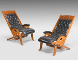 A pair of hardwood ships deckchairs with leather seats and brass fitments. Circa 1920