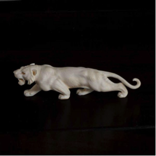 A Meiji period ivory okimono of a stalking tiger with mother of pearl eyes. c1880.