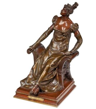 A bronze of an edwardian lady on a window seat