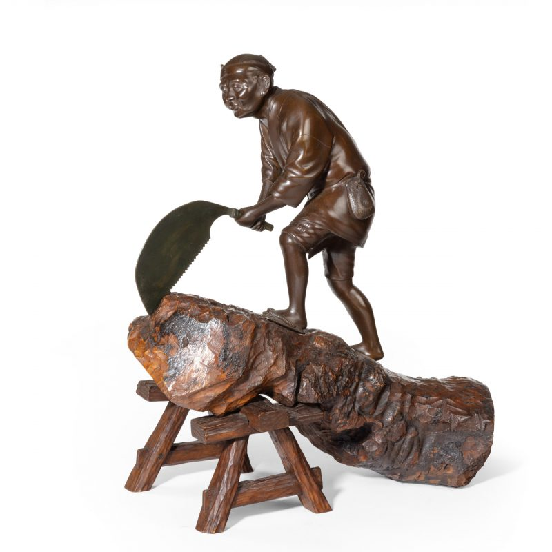 An attractive Meiji period bronze of a woodcutter sawing a large tree trunk