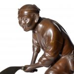 An attractive Meiji period bronze of a woodcutter sawing a large tree trunk mans face