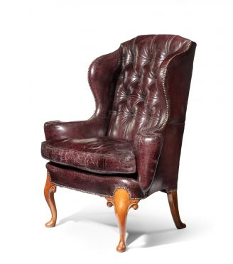 A large George I style burgundy leather wing arm chair