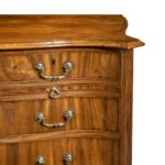 A striking George III serpentine chest of drawers close up