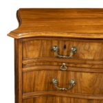 A striking George III serpentine chest of drawers close up left