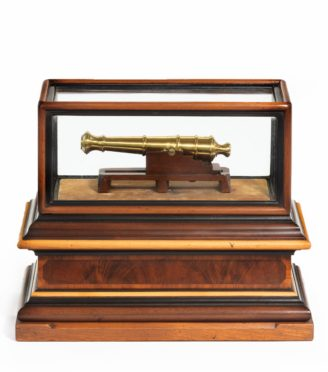 A miniature brass cannon in a presentation case main