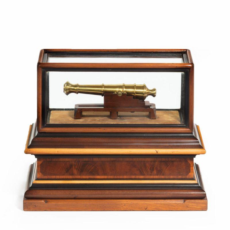 A miniature brass cannon in a presentation case main