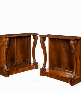 A pair of late Regency flame mahogany console tables