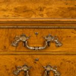 A fine George IV burr oak chest of drawers in the manner of Morel and Seddon handle