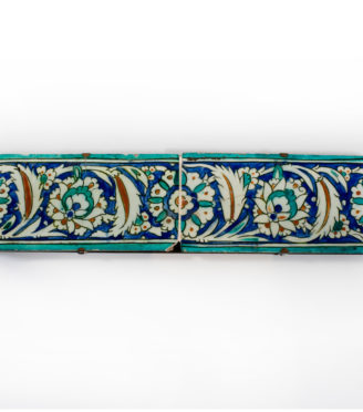 Two Ottoman Iznik border tiles, circa 1600, each of rectangular form, the glazed fritware painted in underglaze turquoise, cobalt blue, black and terracotta red with a continuous band of leafy arabesque scrolls enclosing flowerheads, with turquoise borders mounted Turkish c1600