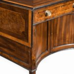 A George III Chippendale-style satinwood Pembroke table, the rectangular top inlaid with a central roundel in burr-yew and further burr-yew panels inlaid into the drop leaves and single frieze drawer, with a pair of concave doors enclosed in the under tier, all raised on inner chamfered square legs terminating in brass caps and castors. English, circa 1790.