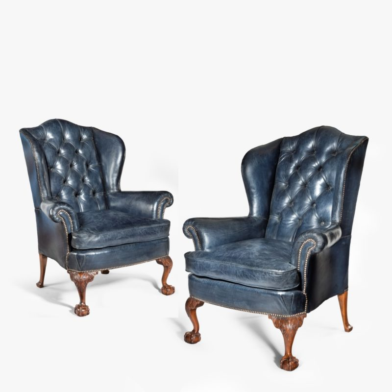 A pair of Chippendale style leather wing armchairs