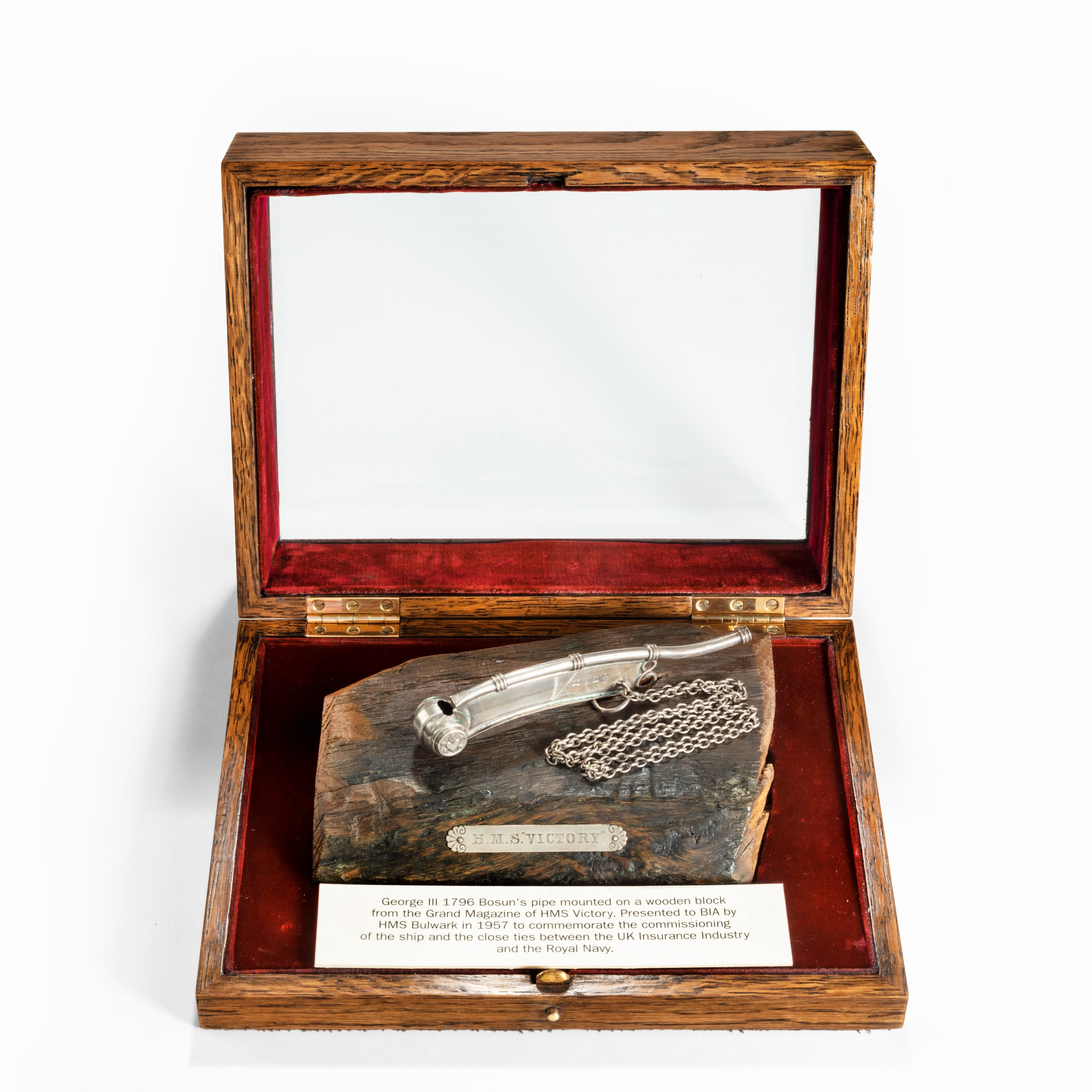 A George III silver bosun's pipe and chain on H.M.S. Victory oak, 1796
