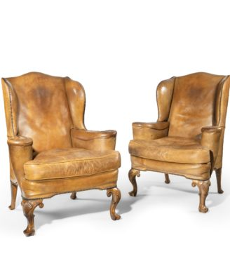 A pair of walnut wing armchairs in the Queen Anne style