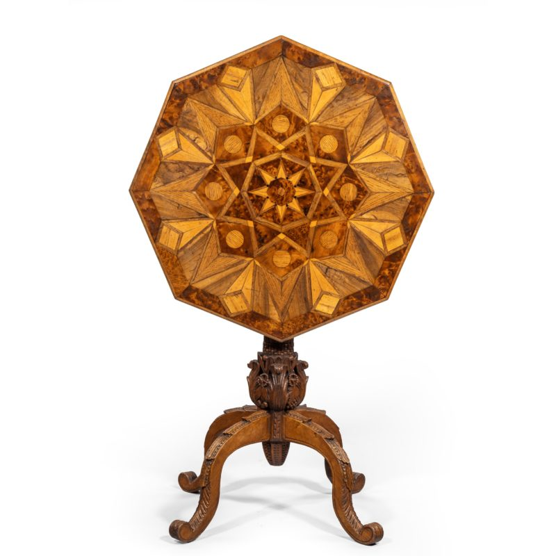 An octagonal indigenous specimen wood marquetry table, the tilt top inlaid on both sides with triangles and diamonds in an overall star design, the woods include yew, oak and elm, on a carved classical column base with four cabriole legs. British, circa 1860.