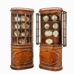 A pair of mahogany shaped display cabinets attributed to Gillows open doors dressed
